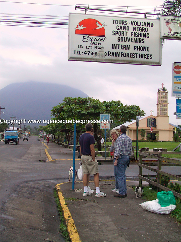 La Fortuna, COSTA RICA , File Photo  Jan 27 2001<br /> A group of tourist  stand outside an organised tour company on the main street of La Fortuna in the Guacanaste province of  COSTA RICA on Jan 27rd, 2001. While clouds partially covers the Arenal volcano, one the the few active volcanoe on earth.