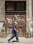 A man walks past graffiti-covered wooden doors along a street, Belgrade, Serbia