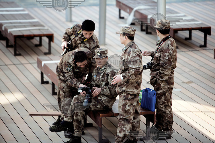 Chinese People's Liberation Army officers relax while looking at photos they've taken at the 2010 World Expo site.
