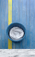 The blue of the wicker laundry basket exactly matches that of the floorboards which are decorated with one bold yellow stripe