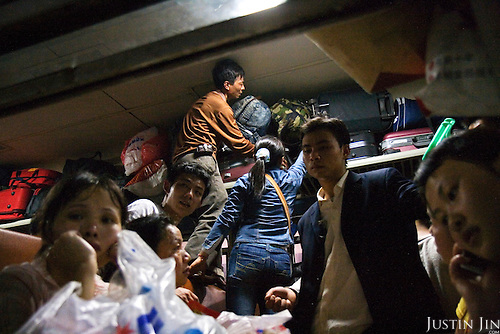 """Workers carrying their possessions squeeze into a train in Guangzhou city, China, as their head home to celebrate new year. .This picture is part of a photo and text story on blue jeans production in China by Justin Jin. .China, the """"factory of the world"""", is now also the major producer for blue jeans. To meet production demand, thousands of workers sweat through the night scrubbing, spraying and tearing trousers to create their rugged look. .At dawn, workers bundle the garment off to another factory for packaging and shipping around the world..The workers are among the 200 million migrant labourers criss-crossing China.looking for a better life, at the same time building their country into a.mighty industrial power."""