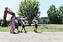A woman walks her children home after school at the  Martin Luther King Jr. Elementary School for Science and Technology in the Lower Ninth Ward, New Orleans, Aug. 27, 2015.