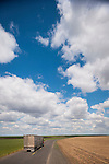 A cattle truck travels a lonely highway beneath a cloudscape in Washington's high desert east of the Columbia River.