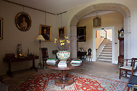 A stone archway opens from the entrance hall to a modest staircase
