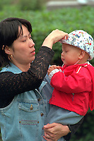 Asian Mom adjusting son's hat age 30 and 1 at Vietnam Wall on Memorial Day. St Paul Minnesota USA