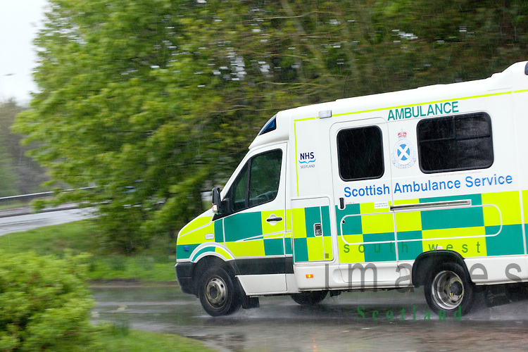 Scottish Ambulance Service bad weather on the A75 road ambulance responding to a emergency call approaching junction at speed in heavy rain UK