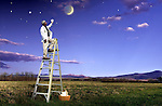 motivational and metaphorical photo of doctor on ladder reaching for star in evening sky