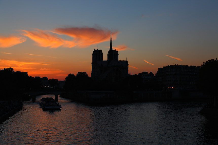 The profile of the back of the church of Notre Dame within its isle in Paris, with a tourist boat passing under the bridge,  in the light of an artistic sunset. Digitally Improved Photo.