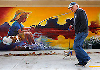 NWA Media/DAVID GOTTSCHALK - 12/15/14 -  Dan Durning walks with Pepi as they pass the new mural by artists Amy Eichler on the north side of the bait shop at Lake Fayetteville.  Durning was walking his parents dogs which also included Abby who was following from behind.