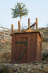 Wooden outhouse with fence and tree on a hillside, Randsburg, Calif.