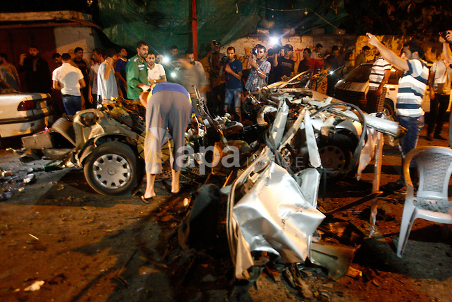 Palestinians check a car hit by an Israeli air strike in Gaza City on July 09, 2014. A Palestinian working for a local news agency in the Gaza Strip was killed on Wednesday night by an Israeli strike on a car full of journalists, according to multiple reports from the war-torn region. Photo by Yasser Qudih