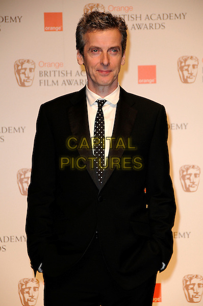 PETER CAPALDI.The Orange British Academy Film Awards 2010 at the Royal Opera House Covent Garden, London, England, UK,.February 21st, 2010 .press awards room pressroom BAFTA BAFTAs half length black suit tie hands in pockets polka dot white shirt .CAP/CAS.©Bob Cass/Capital Pictures