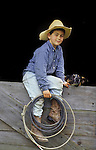 Young cowboy holding a lasso sits in a barn window, his dog alongside.. San Luis Obispo, California   (Garcia Ranch/Joseph/MR)