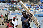A man carries scrap material he scavenged through a camp for homeless families set up on a golf course in Port-au-Prince, Haiti, which was ravaged by a January 12 earthquake.