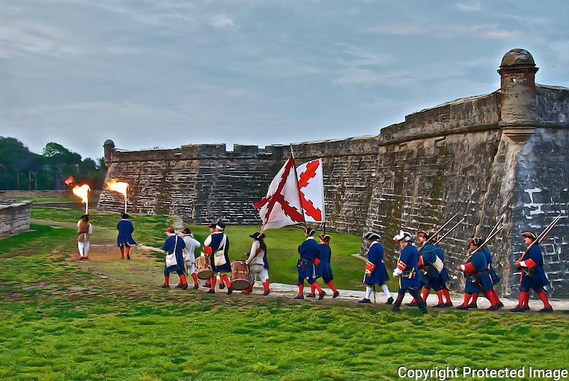 Re-Enactors march in front of the historic Castillo de San Marco on a cloudy spring evening. The coquina fort is located on the Matanzas Bay in beautiful downtown St. Augustine, Florida.