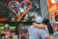 "As a singular example of how both Times Square and human behavior have changed since Eisenstaedt's photograph, a couple from the V-J Day kiss-in marvel at themselves on a display billboard near the exact location of the historic shot. To mark the 70th anniversary of the surrender of the Japanese ending WWII, the Times Square Alliance and ""Spirit of '45,"" a WWII legacy organization, hosted a kiss-in with members of the public invited to imitate the sailor and nurse in Alfred Eisenstaedt's famous photograph.  (PHOTO: Abin Lohr-Jones/BRAZIL PHOTO PRESS)"