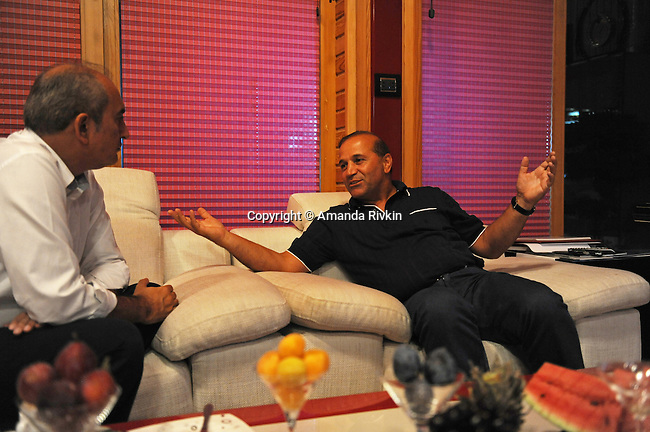 Ibrahim Ibrahimov (right) sits and talks with a Turkish business associate, M. Tayfur Ozturk, after dinner in his home between Sangachal and Sahil, Azerbaijan on August 16, 2012.