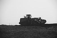 Daytime landscape view from a train of a bulldozer driving on top of a mound of coal near Dàtóng Shì Chéng Qū in Shānxī Province, China  © LAN