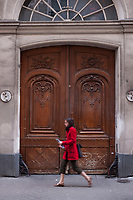 A stylish young woman in a red coat, holding a magazine in her hands, walks past an ornate door in Paris, France.