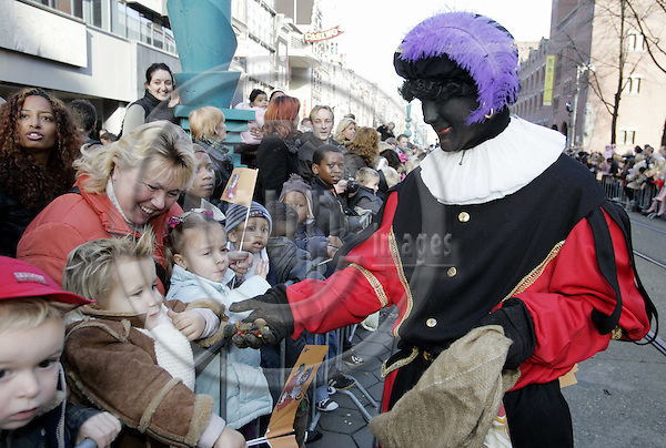 AMSTERDAM - NETHERLANDS - 14 NOVEMBER 2004 -- Arrival of Saint Nicholas to Amsterdam with his helpers Zwarte Pieten (black Peters). -- A Zwarte Piet, dressed in colorful a Moorish costume giving candies to children. -- PHOTO:  EUP-IMAGES / JUHA ROININEN