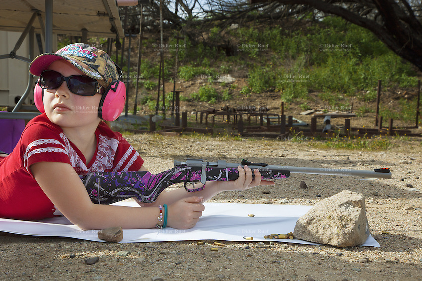USA. Arizona state. Kearny town. Copper Basin Sportsmen's Club. Dakota Stonecipher, 8 years old, is a little girl. She is training her shooting skills with her Henry Mini Bolt .22 - Single Shot Bolt Action Rifle. The rifle helps young shooters be successful on shots, thanks to the Williams Fire fiber-optic sights that make it easy to aim and the wraparound checkering that offers a firm grip, even for little hands. The rifle is a single-shot, European-style bolt action and has a manual safety switch. Copper Basin Sportsmen's Club is a membership Range complex which purpose is to promote the sport of shooting and providing a safe, fun, family oriented environment. A firearm is a portable gun, being a barreled weapon that launches one or more projectiles often driven by the action of an explosive force. Most modern firearms have rifled barrels to impart spin to the projectile for improved flight stability. The word firearms usually is used in a sense restricted to small arms (weapons that can be carried by a single person). The right to keep and bear arms is a fundamental right protected in the United States by the Second Amendment of the Bill of Rights in the Constitution of the United States of America and in the state constitutions of Arizona and 43 other states. 29.01.16 © 2016 Didier Ruef