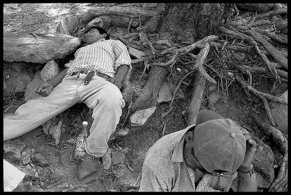Oaxaca, Mexico.<br />  Along the bank of the Atoyac River, construction workers rest and sleep off the cheap mezcal (alcohol) they had been drinking since 9am.