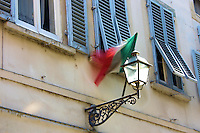 The Italian flag movement is captured with a slow shutter speed against the shutters of second level residences