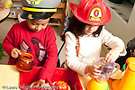 Education preschool 3-4 year olds pretend play kitchen area boy and girl playing side by side wearing dressup hats pilot and fire hat horizontal parallel play