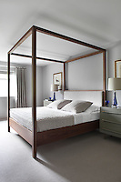 The bedroom is furnished with a simple, cube-like four-poster bed flanked by matching chests of drawers and bedside lamps