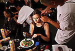 A model eats a meal as she is prepared for the runway by a hairdresser during the Desigual presentation during New York Fashion Week in New York, Thursday September 10, 2015. AFP PHOTO/TREVOR COLLENS