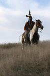 A Native American Indian man sitting bareback on a horse in traditional Sioux Indian clothing in South Dakota