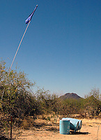 A Flag flying high is a marker for a water station, to let those crossing the desert know that they can get water here, south of Tucson on a private part of land.  This photo was taken during a ride along with Borstar Border Patrol Agents south of Tucson..Photo by AJ Alexander