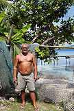 FRENCH POLYNESIA. Atger on his own island, Atger Island, standing and fixing his fishing nets.