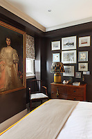 A traditional bedroom with brown painted walls. A collection of paintings is arranged on the wall above an antique chest of drawers.