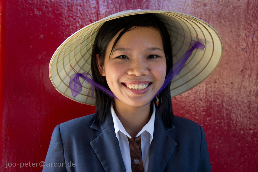 portrait of a smiling girl with traditional vietnamese leaf-hat in front of red temple  door in the city Hoi An, Vietnam