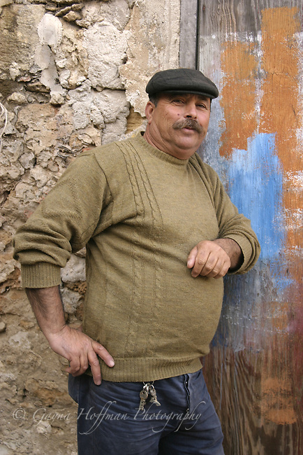 Sicilian fisherman leaning against wall of old building. Portopalo Di Cap Passero, Italy