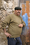 Sicilian fisherman leaning against wall of old building. Portopalo Di Cap Passero, Italy