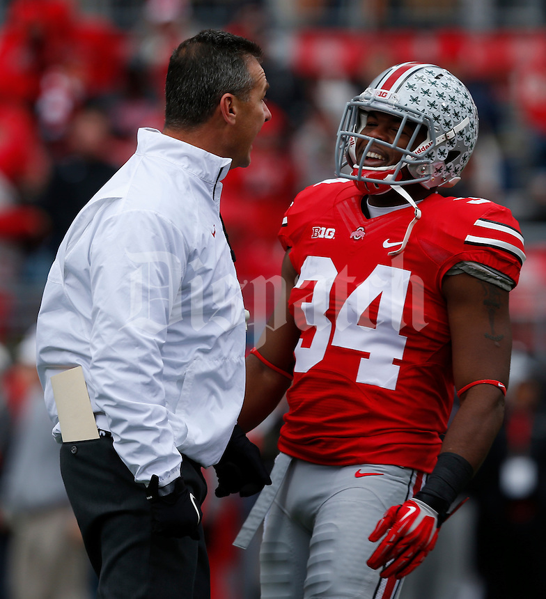 Ohio State Buckeyes head coach Urban Meyer talks with Ohio State Buckeyes running back Carlos Hyde (34) during pre-game warm-ups before Saturday's NCAA Division I football game against Indiana at Ohio Stadium in Columbus on November 23, 2013. (Barbara J. Perenic/The Columbus Dispatch)