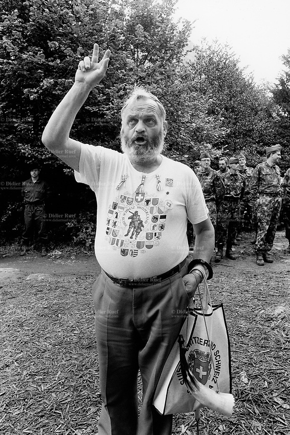 Switzerland. Canton Uri. Rütli. 1 August 1991. Swiss national holiday. Public holiday. A man with a beard takes an oath of allegiance to Switzerland by holding up his three fingers. He wears a t-shirt with: William Tell (Wilhelm Tell - Guillaume Tell), his crossbow and his son; the flags of the 26 swiss cantons. He holds on his arm a bag with ta Swiss flag and the words Suisse, Schweiz, Switzerland. A group of soldiers in military uniforms and a policeman. Rütli (or Grütli in French) is a mountain meadow in the Seelisberg municipality of the Swiss canton of Uri. Here the oath of the Rütlischwur is said to have occurred, the legendary turning-point in the pursuit of independence. Every August 1, on the Swiss National Day, the oath is re-enacted to commemorate the forming of the Old Swiss Confederacy. Rütli is the birthplace of the Swiss Confederation. 1.08.1991 © 1991 Didier Ruef