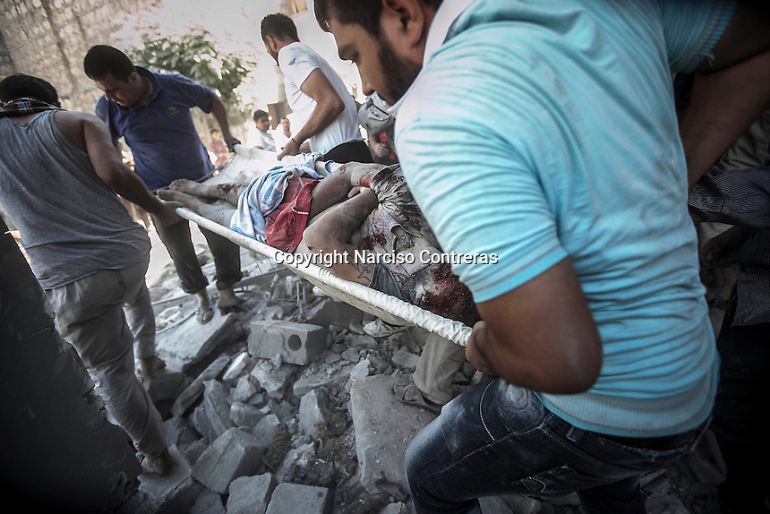 Syrian civilians carry up the body of a dead man that was found among the debris of a demolished house building as they take the dead body to the hospital. The victim was killed by aircraft shelling at his home which was targeted by one army plane at Tarik Albab neighborhood in the northeastern of Aleppo City. The Syrian army is carrying out aircraft shellings over residential areas throughout Aleppo City, killing hundreds of civilians in its attempt to sweep out the rebels.