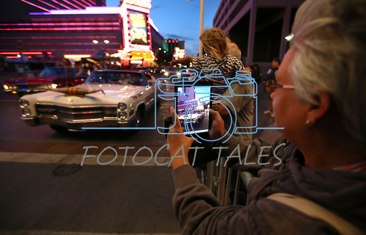 Gerry Combes, of Powell River, Canada, takes pictures as classic cars cruise in downtown Reno, Nev., on Wednesday night, Aug. 7, 2013, during the official Kick-Off Cruise of Hot August Nights. (AP Photo/Cathleen Allison)