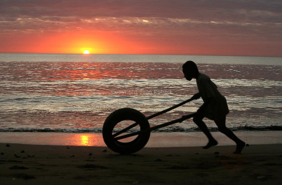 Enfant jouant au pneu sur la plage de Sohoa au coucher du soleil