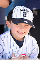 Young New York Yankees fan wearing a Derek Jeter hat looking for autographs before a spring training game against the Philadelphia Phillies on March 1, 2014 at Steinbrenner Field in Tampa, Florida.  New York defeated Philadelphia 4-0.  (Mike Janes/Four Seam Images)