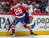 WASHINGTON, DC - JANUARY 31: Johnny Boychuk #55 of the New York Islanders  and Brendan Leipsic #28 of the Washington Capitals  battle along the boards during a game between New York Islanders and Washington Capitals at Capital One Arena on January 31, 2020 in Washington, DC.