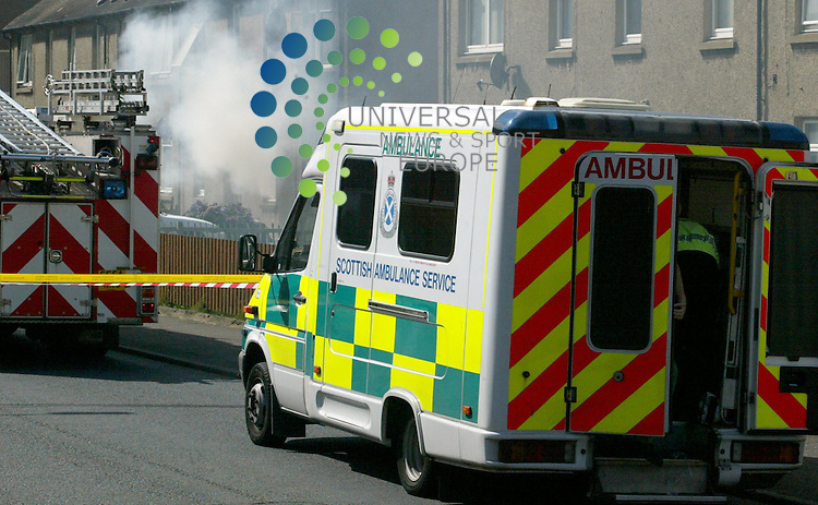 Smoke belches from the house explosion at 57 Walker Av Barassie Troon as Mr Joe McDougal receives  medical treatment in the ambulance
