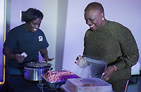NWA Democrat-Gazette/CHARLIE KAIJO Angie Henry (from right) pictured with Sheena Owens of Springdale smiles as she opens a container with hot food she will serve to guests on Monday, January 1, 2018 at the World Event Center in Rogers. The event Trappy New Year is a New Years day party started by Henry of Bentonville, a radio host on KDIV 98.7. <br />