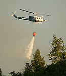 Rogers Helicopters' Bell 212 dumps a bucket of water on the left flank of the Middle Bar Fire in Calaveras County near sunset.