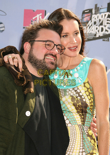 KEVIN SMITH & JENNIFER SCHWALBACH SMITH.2007 MTV Movie Awards held at the Gibson Amphitheater, Universal City, California, USA..June 3rd, 2007.half length green blue yellow pattern dress married husband wife glasses beard facial hair .CAP/ADM/RE.©Russ Elliot/AdMedia/Capital Pictures *** Local Caption *** ...