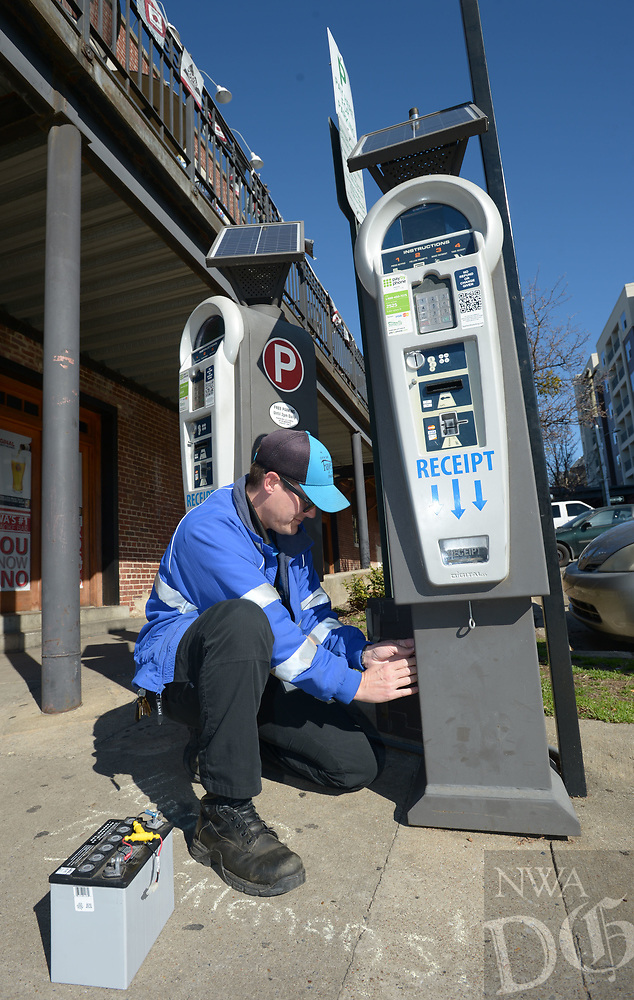 NWA Democrat-Gazette/ANDY SHUPE<br /> Luke Bouxsein, a parking enforcement officer with the city of Fayetteville, changes a battery Friday, March 2, 2018, on a parking pay station off West Avenue in Fayetteville. Consulting firm Nelson/Nygaard has completed a nearly 2-year-long study of parking downtown. On Tuesday, the City Council will discuss implementing the first phase of the study's recommendations. One of the first steps of the recommended downtown parking plan is rebranding parking enforcement officers as customer servers, rather than ticket-writers.
