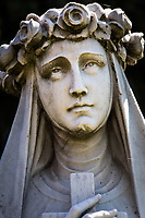 A close-up of the face of a Saint Rose of Lima statue that stands in a landscaped setting facing St. Rose Hospital in Hayward, California.